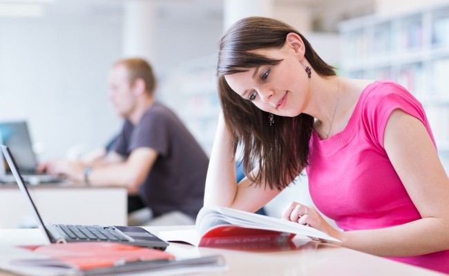 In the library – pretty female student with laptop and books